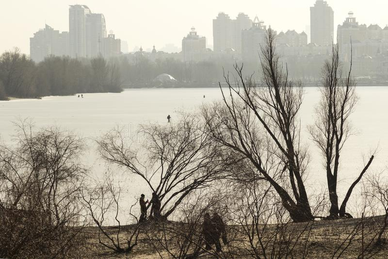 Floden täckas med is På bankerna av träden ett par av folk nära träden På horisonten av byggnaden arkivbild