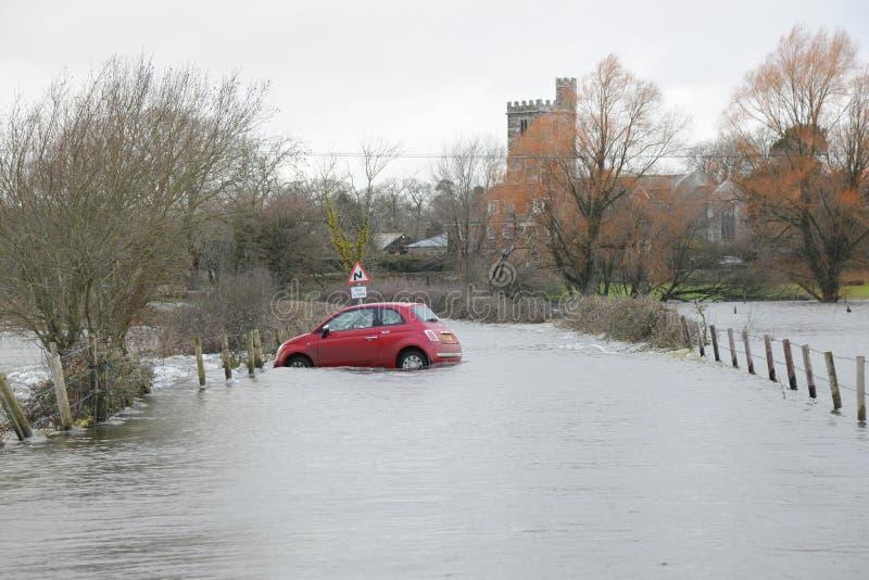 Floder överväldigar den röda bilen royaltyfria foton
