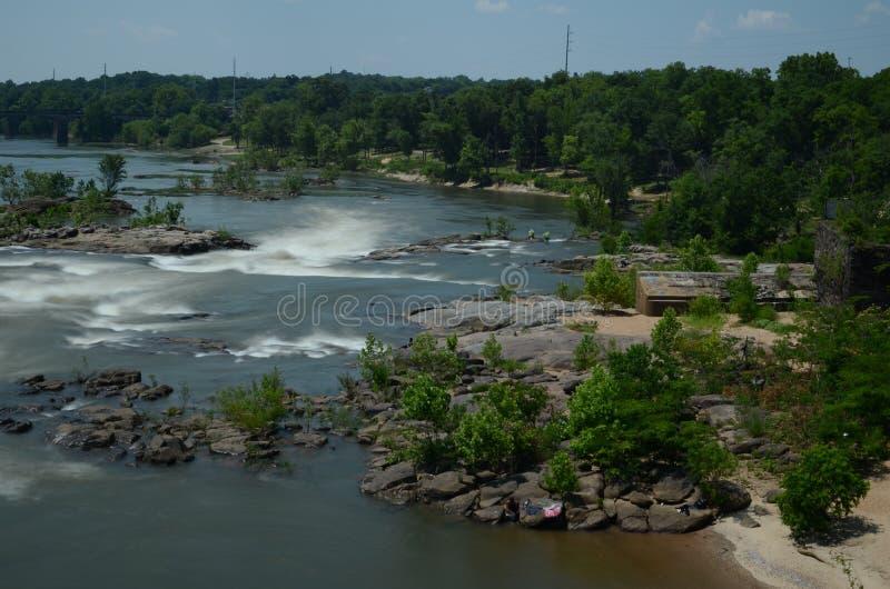 Flodforsar i rörelse med trän och gräsplan runt om den royaltyfri foto