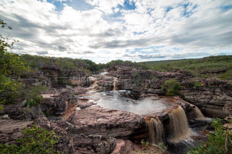 Flodkanjon och vattenfall, gröna tropiska träd och molnig himmel arkivfoto