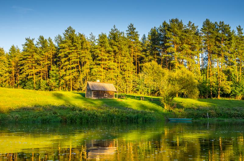 Flodlandskap i vårtid, liten träkabin royaltyfri bild