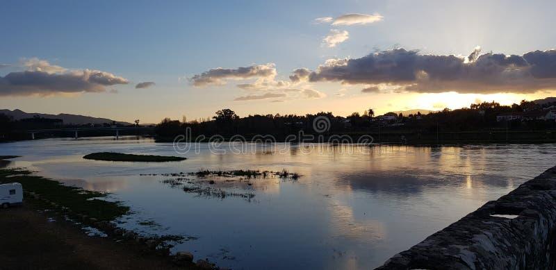 Flodsida medan solnedgång royaltyfria bilder