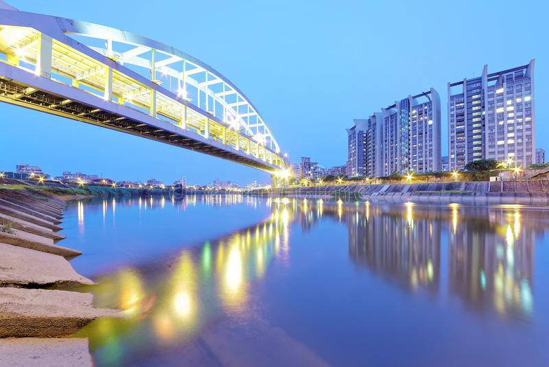 Flodstrandbyggnader och den berömda HuanDong regnbågebron över den Keelung floden på skymning i Taipei Taiwan, Asien arkivfoto