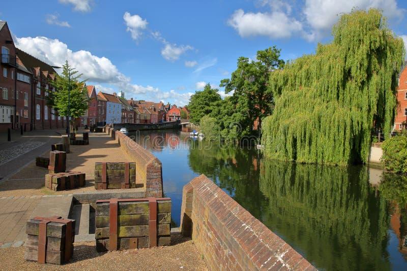 Flodstrandfloden Wensum i Norwich Norfolk, UK med färgrika hus på vänstra sidan och den Fye bron i bakgrunden royaltyfri foto