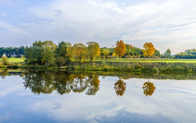 Flodstrandplats med träd som reflekteras i floden Tauber fotografering för bildbyråer