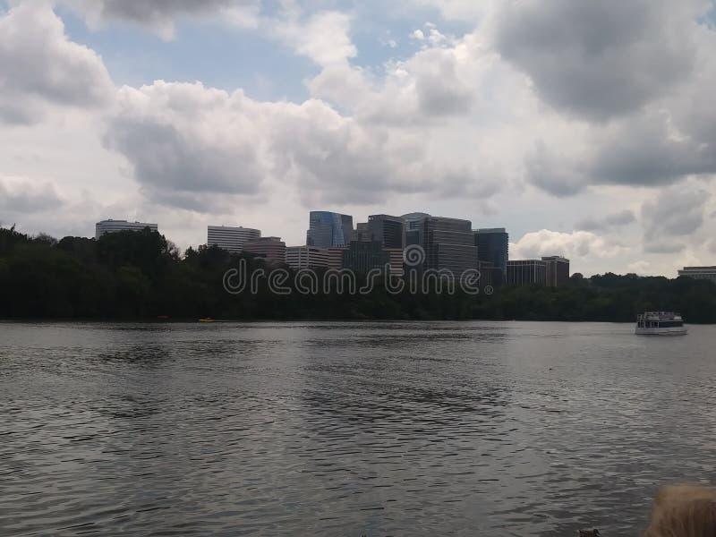 Flodstrandsikt med moln och byggnader royaltyfri foto