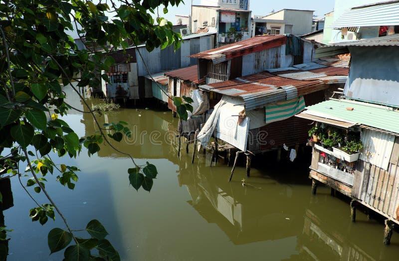 Flodstrandslumkvarteret, hus nära förorenade floden royaltyfri fotografi