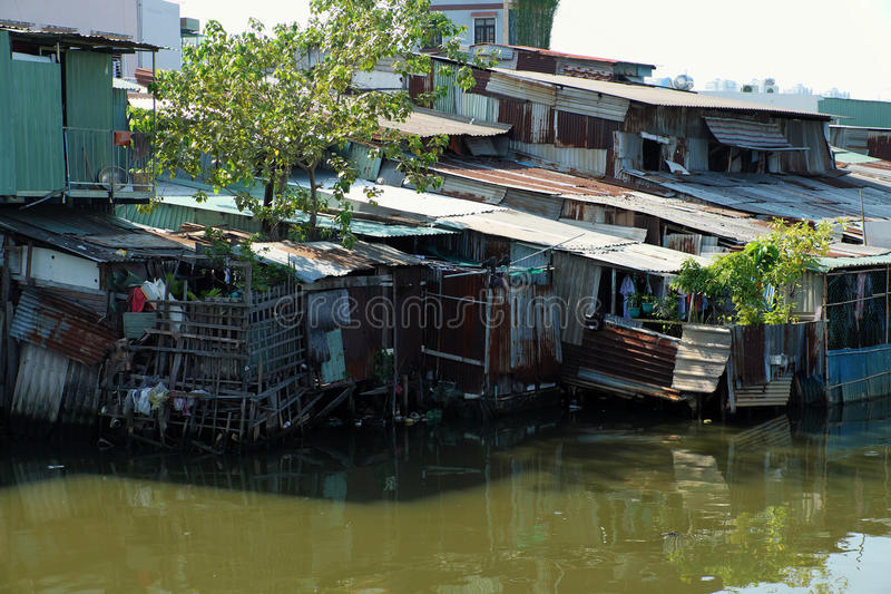 Flodstrandslumkvarteret, hus nära förorenade floden royaltyfri bild
