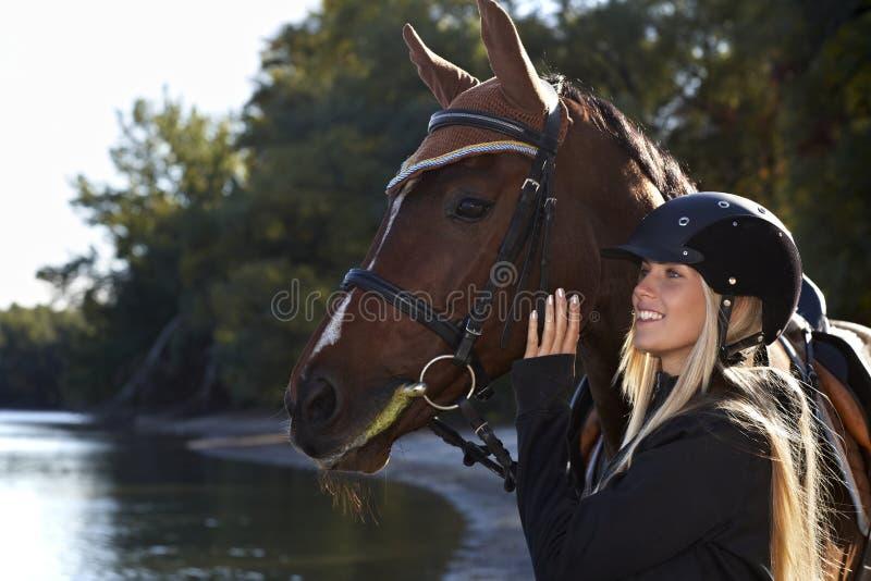 Flodstrandstående av ryttaren och hästen fotografering för bildbyråer