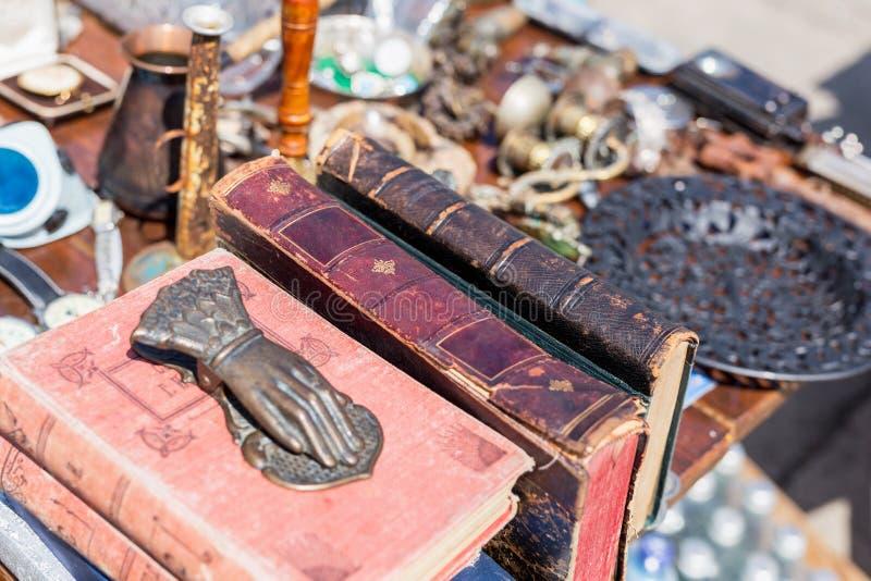 Flohmarktzähler Alte Weinlese alterte Buch-, Bronzetürklopfer und andere Retro- Waren an der Tauschbörse stockbild