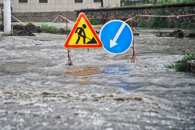 Flood on a city street after heavy rain. Flooded traffic signs. The effects of global warming. Disaster royalty free stock images