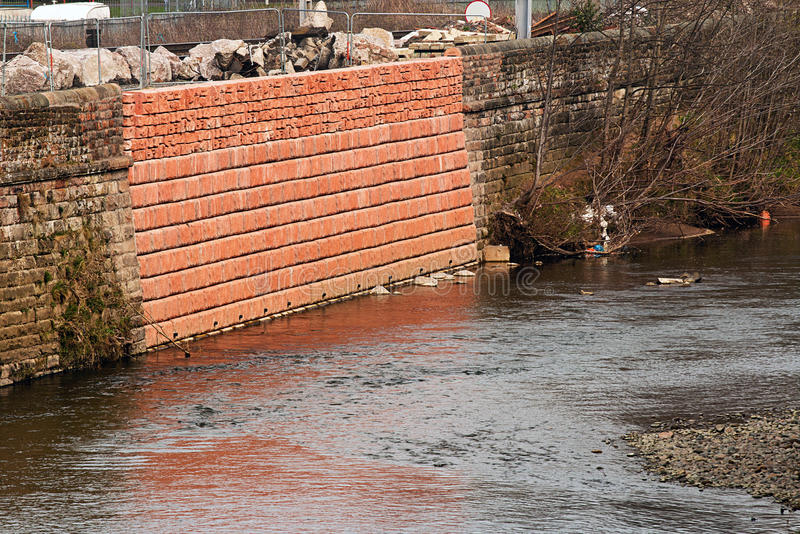 Flood damage repair. Damaged flood wall that has been repaired due to a recent breach broke the banks of the river during a storm stock image