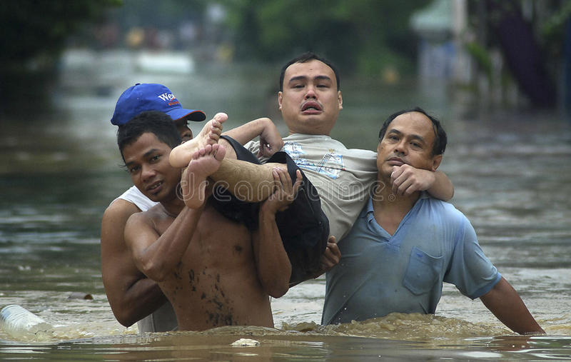 FLOOD EVACUATION. Volunteers evacuate a disabled young man from heavy flooding that hit Bengawan Solo River Basin, at Solo, Java, Indonesia stock photo