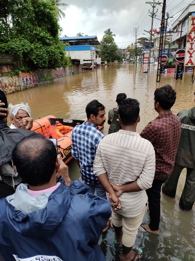 2019 flood in Nilambur, Kerala. NILAMBUR, KERALA, INDIA - AUGUST 08, 2019: People gathered near the flood affected street in Janathapadi, Nilambur. Shops and stock photo