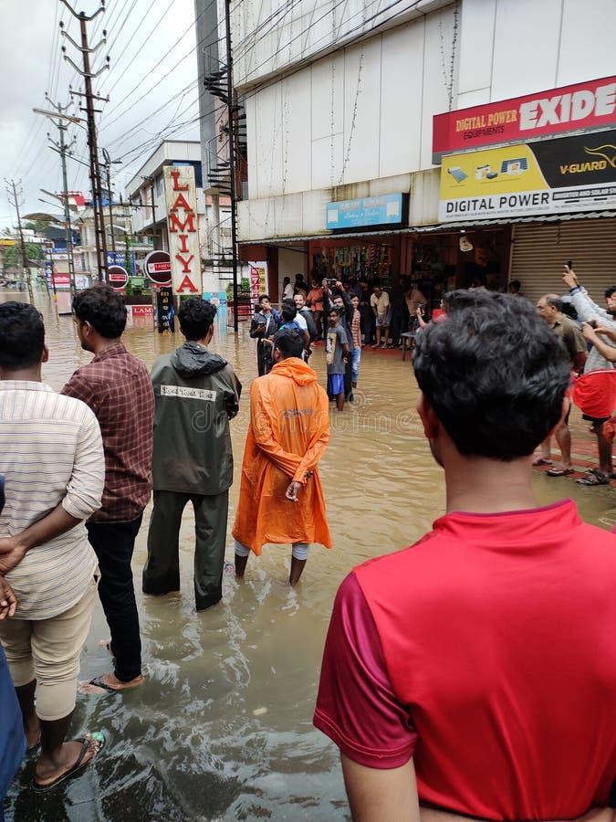 2019 flood in Nilambur, Kerala. NILAMBUR, KERALA, INDIA - AUGUST 08, 2019: People gathered near the flood affected street in Janathapadi, Nilambur. Shops and royalty free stock photos