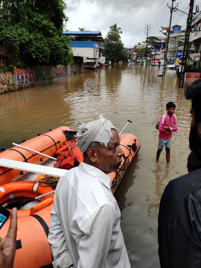 2019 flood in Nilambur, Kerala. NILAMBUR, KERALA, INDIA - AUGUST 08, 2019: People gathered near the flood affected street in Janathapadi, Nilambur. Shops and royalty free stock photo