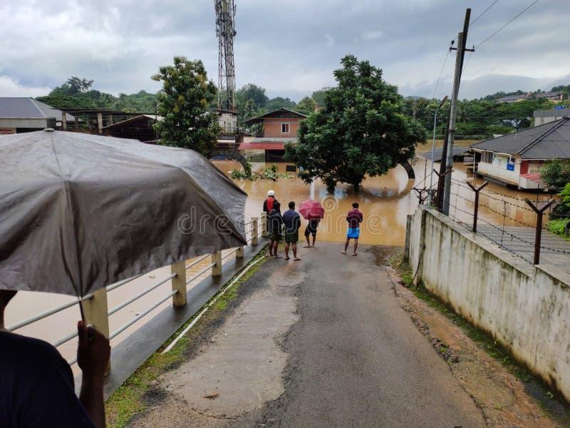 2019 flood in Nilambur, Kerala. NILAMBUR, KERALA, INDIA - AUGUST 09, 2019: People gathered near the flood affected street in Janathapadi, Nilambur. Shops and stock photo