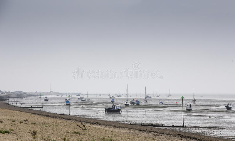 Flood tide at Southend. Motor boats and yachts beached on the sands at Southend on the Thames estuary beginning to float as the tide floods in royalty free stock photography
