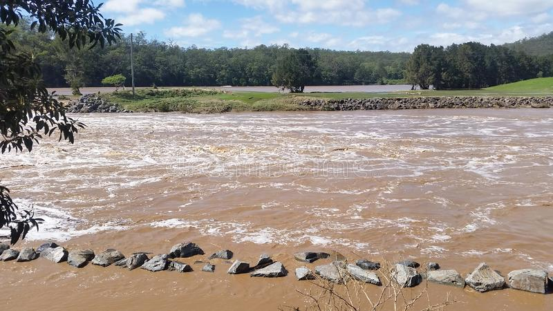 Floodwaters Oxenford, Queensland, Australia. Flood Waters at the Coomera River Weir, Queensland Australia royalty free stock image