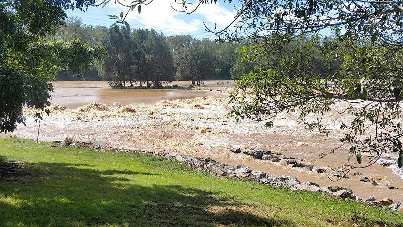 Floodwaters Oxenford, Queensland, Australia. Flood Waters at the Coomera River Weir, Queensland Australia royalty free stock photo