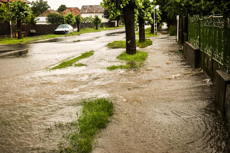 Flooded city street after thunderstorm. The road and the sidewalk are covered with water after the massive rain. The flood makes stock photography