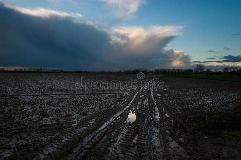 The road goes ever on... A flooded country road, in the flemish country side, against a clouy sky royalty free stock images