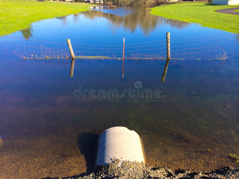 Flooded Farm Creek. Water is very high after some recent rainfall and this small farm creek is at flood stage stock photo