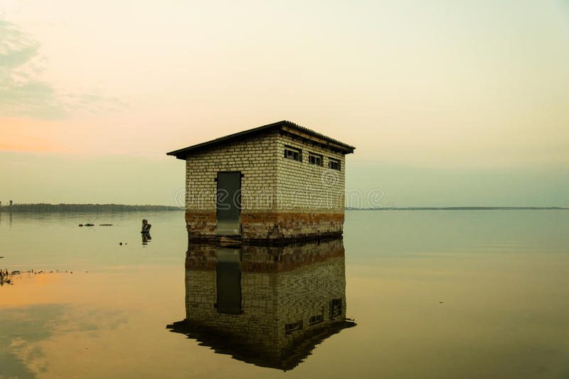 Flooded house. Lonely, the requested and flooded house by the lake royalty free stock images