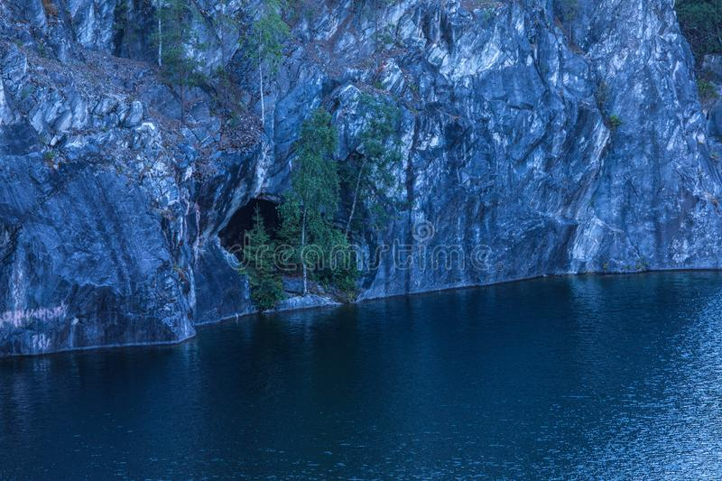 The flooded marble quarry. The cliffs of marble and the water of lake below. stock photography
