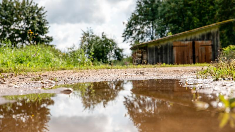 Flooded, muddy country road after rainfall and storm. Natural disaster and consequences of global warming royalty free stock photo