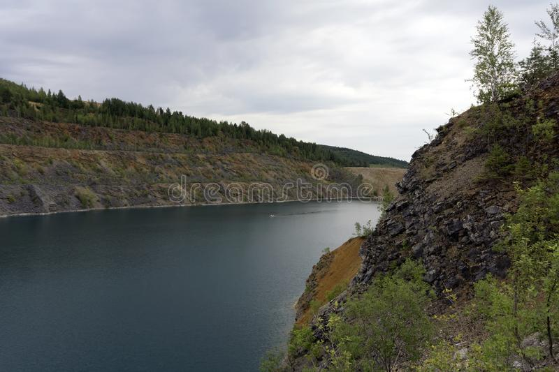 Flooded quarry with blue water. Lake with blue water, a place of recreation formed on the site of old abandoned quarry stock images