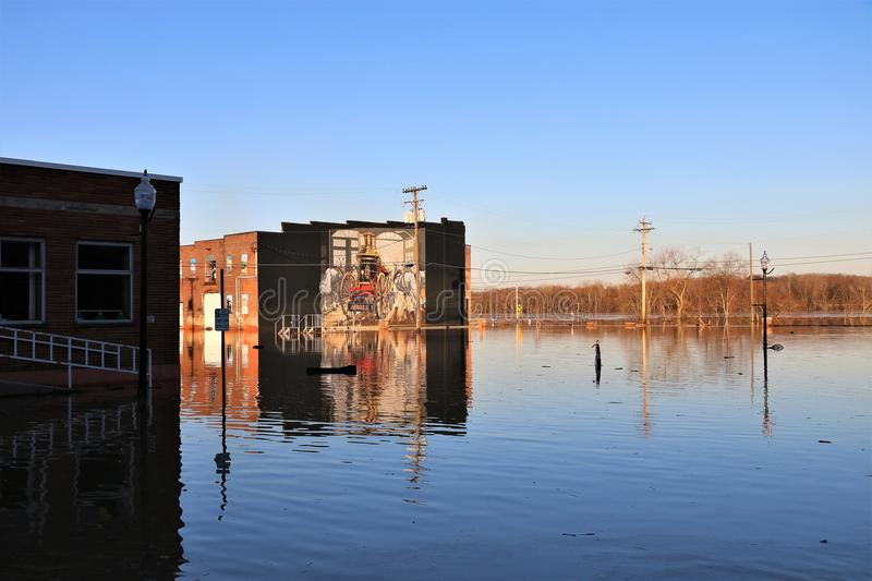 Flooded river outside building in Aurora, Indiana. February 2018 flooding of Aurora, Indiana from the Ohio River. Flood waters outside building. Sunset. Colorful stock image