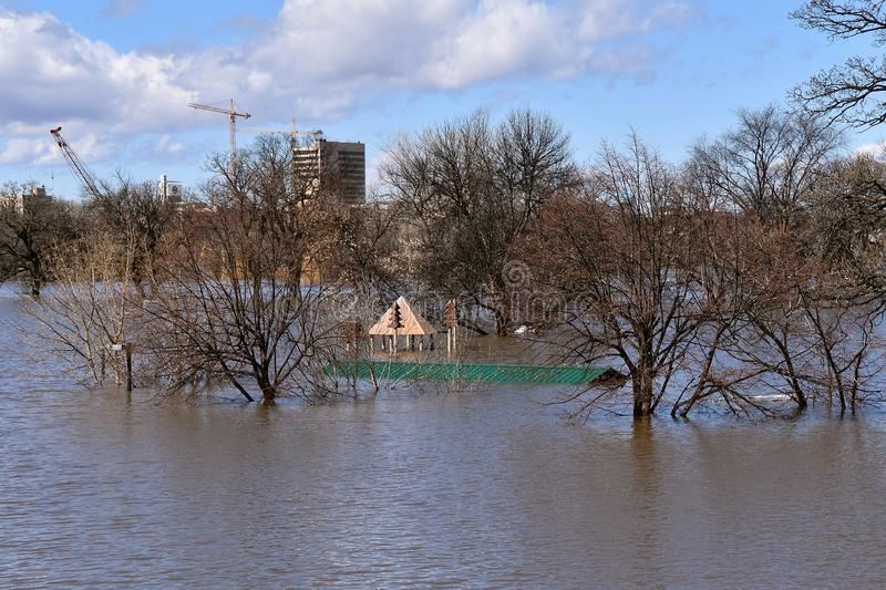 Flooded river during spring thaw. A flooded over river in an urban environment floods a city park leaving only a roof of a picnic shelter exposed stock photo