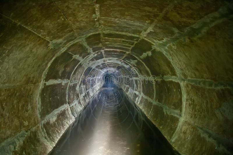 Flooded round sewer tunnel is reflecting in water stock images