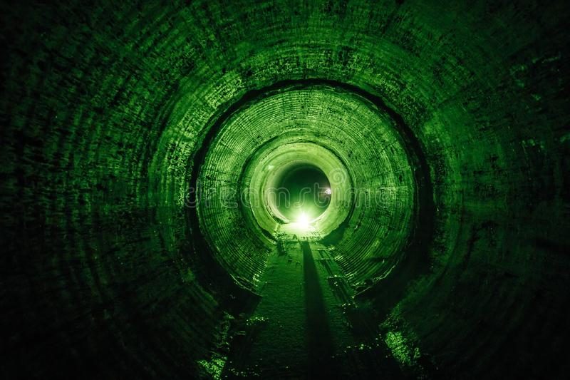 Flooded round underground drainage sewer tunnel with dirty sewage water green illuminated royalty free stock images