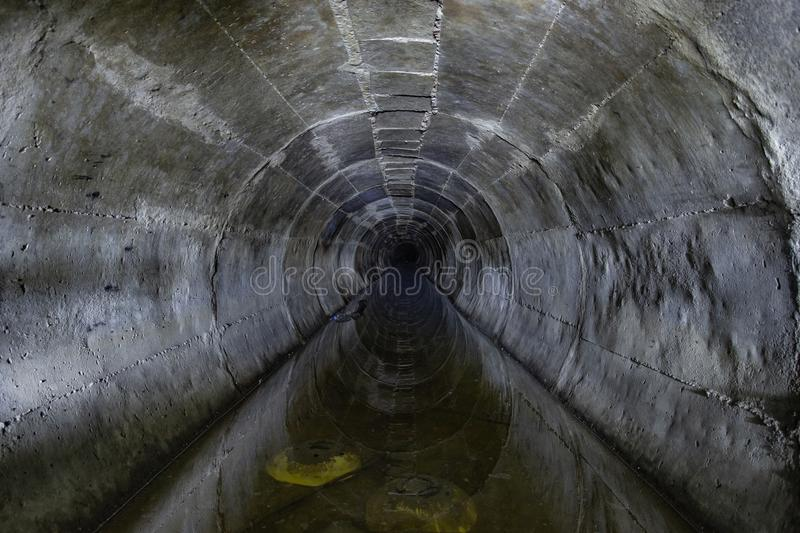 Flooded round underground drainage sewer tunnel reflecting in dirty sewage water royalty free stock image