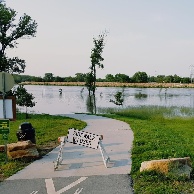 Flooded sidewalk pathway in park with Closed sign and trees and grass in the background stock image