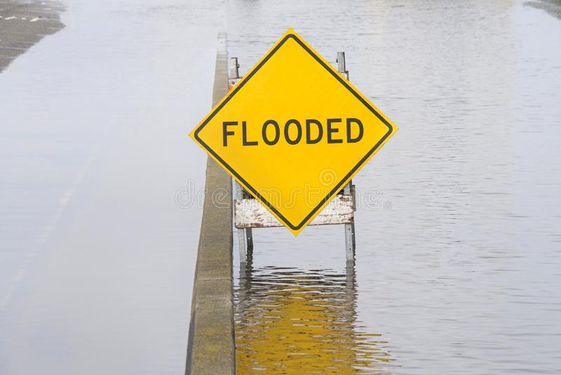 Flooded sign in middle of water flooding street and adjacent parking area. Flooded sign in the middle of standing water in the road and on the adjacent parking royalty free stock images