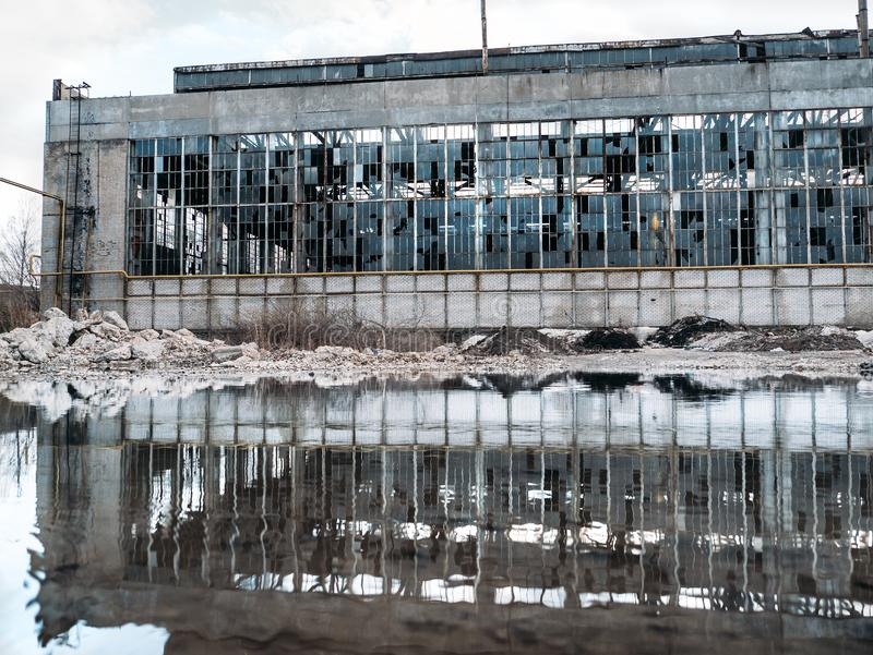 Flooded  territory of abandoned ruined industrial factory building with broken facade and windows, reflection in water. Toned stock photography