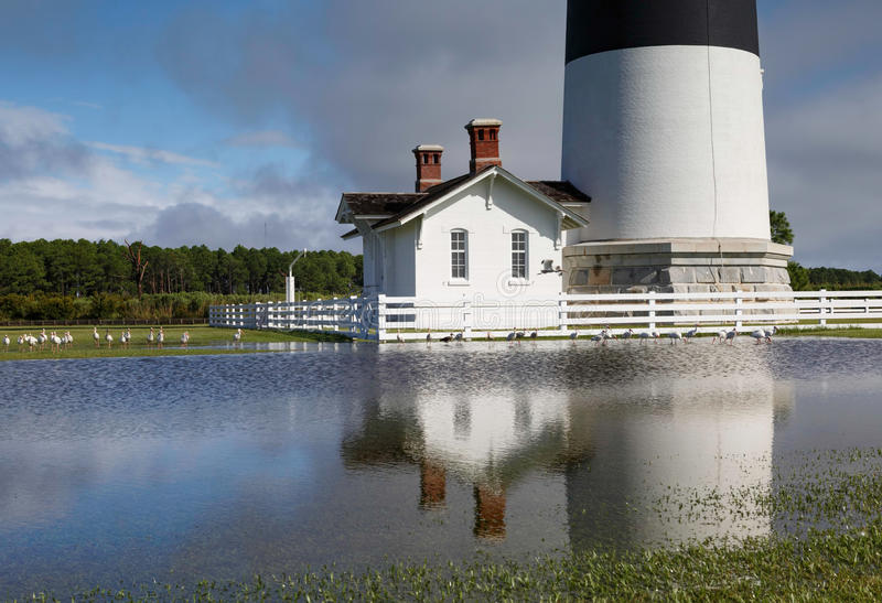 Flooding at Bodie Island Lighthouse North Carolina. Base of the Bodie Island lighthouse reflected in puddled water flooded on the grounds after a huge hurricane stock image