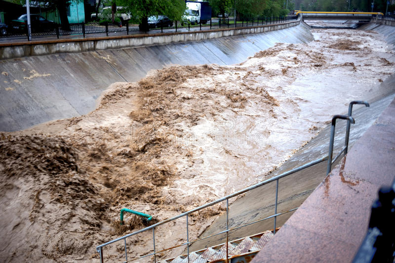 Flooding on mountain river in city. Flooding on the mountain river after heavy rains in the city of Almaty, Kazakhstan, Central Asia stock images