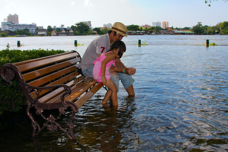 Flooding near the Chao Phraya River in Bangkok. BANGKOK THAILAND - OCTOBER 25 :Flooding in the park near the Chao Phraya River in Bangkok. Thai man with a little stock photography