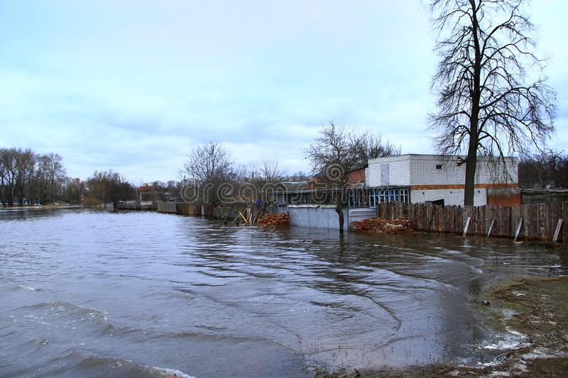Flooding of river in spring in town during melting of snow. Natural disaster. Flooding of river in spring in town during melting of snow. Flooding city. Flood stock image