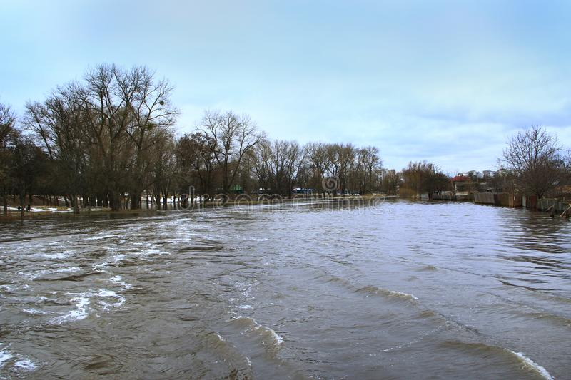 Flooding of river in spring in town during melting of snow. Natural disaster. Flooding of river in spring in town during melting of snow. Flooding city. Flood stock photo
