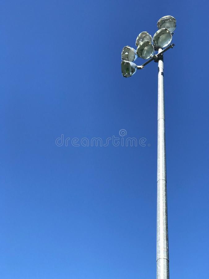 A floodlight at the top of a large metal pylon against a bright blue sky royalty free stock photos