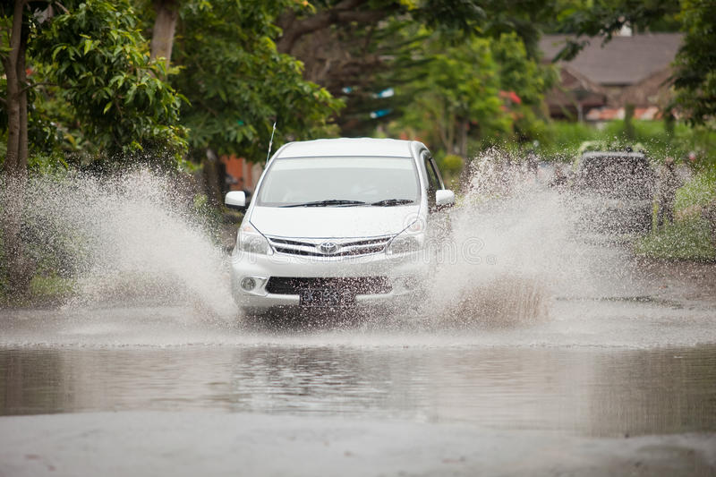Floods. LAKE BATUR, BALI - JANUARY 21. Car driving through flooded street after downpour on Lake Batur on January 21, 2012 in Bali, Indonesia. Weather patterns stock photography