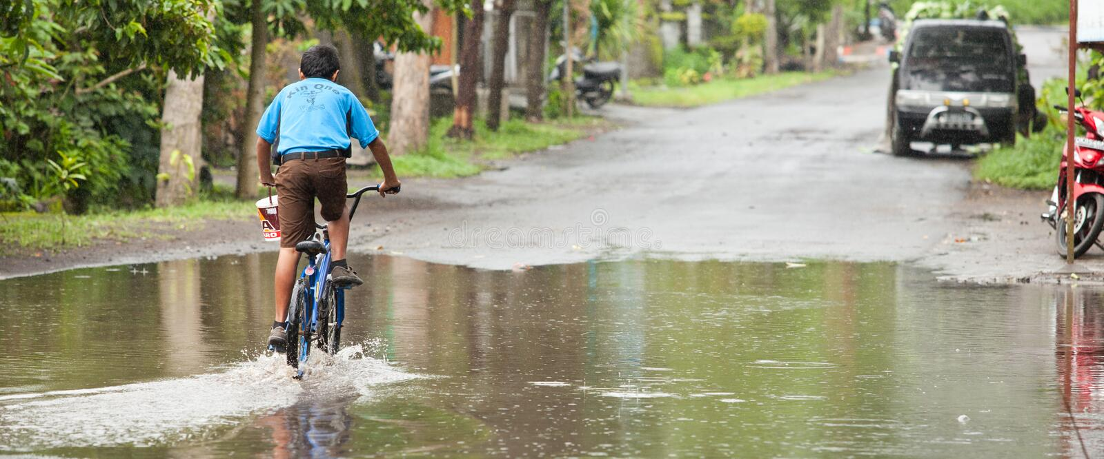 Floods. LAKE BATUR, BALI - JANUARY 21. Kid cycling through flooded street after downpour on Lake Batur on January 21, 2012 in Bali, Indonesia. Weather patterns stock images