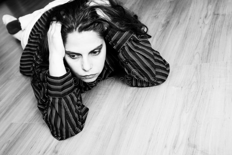 On the floor. Young woman lying down on the wooden floor royalty free stock photos