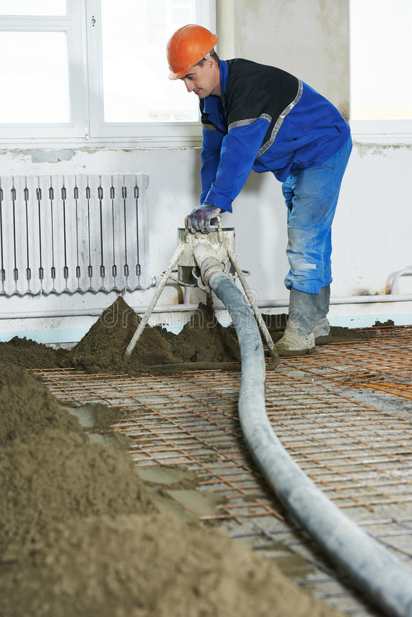 Floor cement covering plastering work. Plasterer at indoor floor concrete cement covering royalty free stock photography