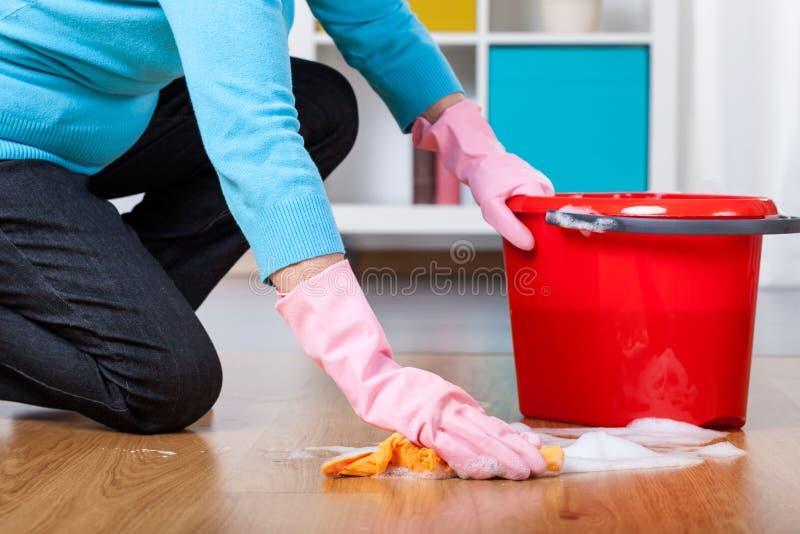 Floor cleaning. Elderly woman kneeling, doing floor cleaning at home stock photo